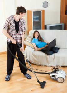 Man cleaning while girl lying on couch with laptop computer