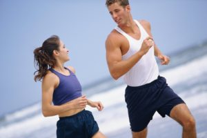 Couple exercising and running on beach
