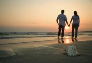 Happy couple on beach holding hands