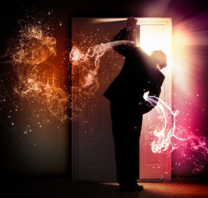 Man opening door and surrounded by fire and light