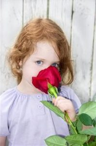 Young redheaded girl stopping to smell a rose