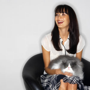 Woman sitting on chair holding a cat and laughing