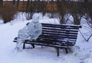 Anthropomorphic ice sculpture sitting on bench representing cold weather survival