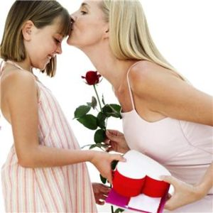 Daughter receiving a kiss after giving rose to grateful mother